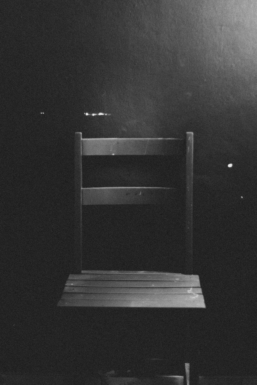 black and white image of an empty chair set against a wall