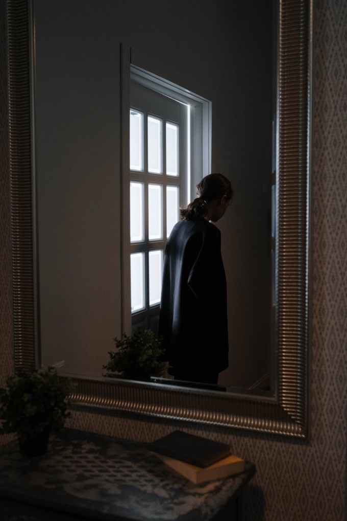 The back view of a person wearing black, and with dark hair in a ponytail, standing beside a lit door. The image is seen through a mirror.